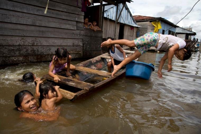 En esta imagen del 19 de abril de 2015, niños jugando en un bote en el agua ante sus casas en el barrio de Belén en Iquitos, Perú. Esta empobrecida comunidad peruana conocida como
