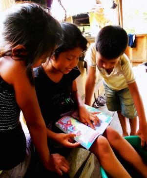 Violetta Pamela e Christian leggono un libro che gli abbiamo regalato. E' il primo libro che possiedono in casa.